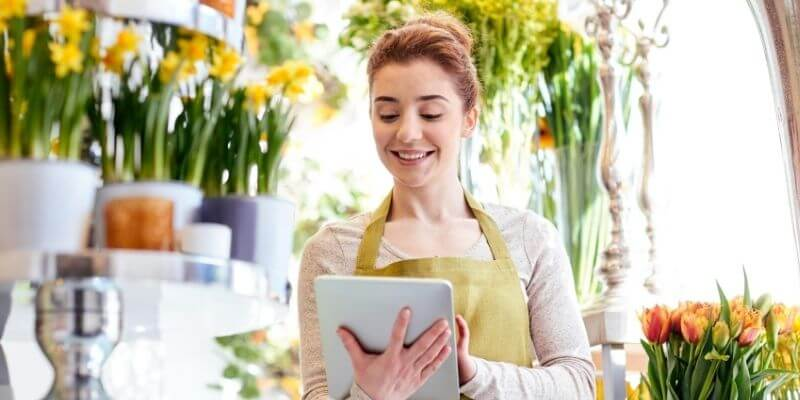 Female business owner using tablet to apply for small business funding in a flower shop